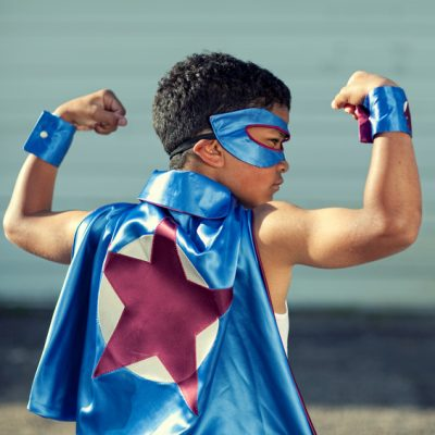 Find Your Child's Strengths: Portrait of a young African American superhero flexing his muscles. Vanquishing evil in a single afternoon. It is never too early to be super.