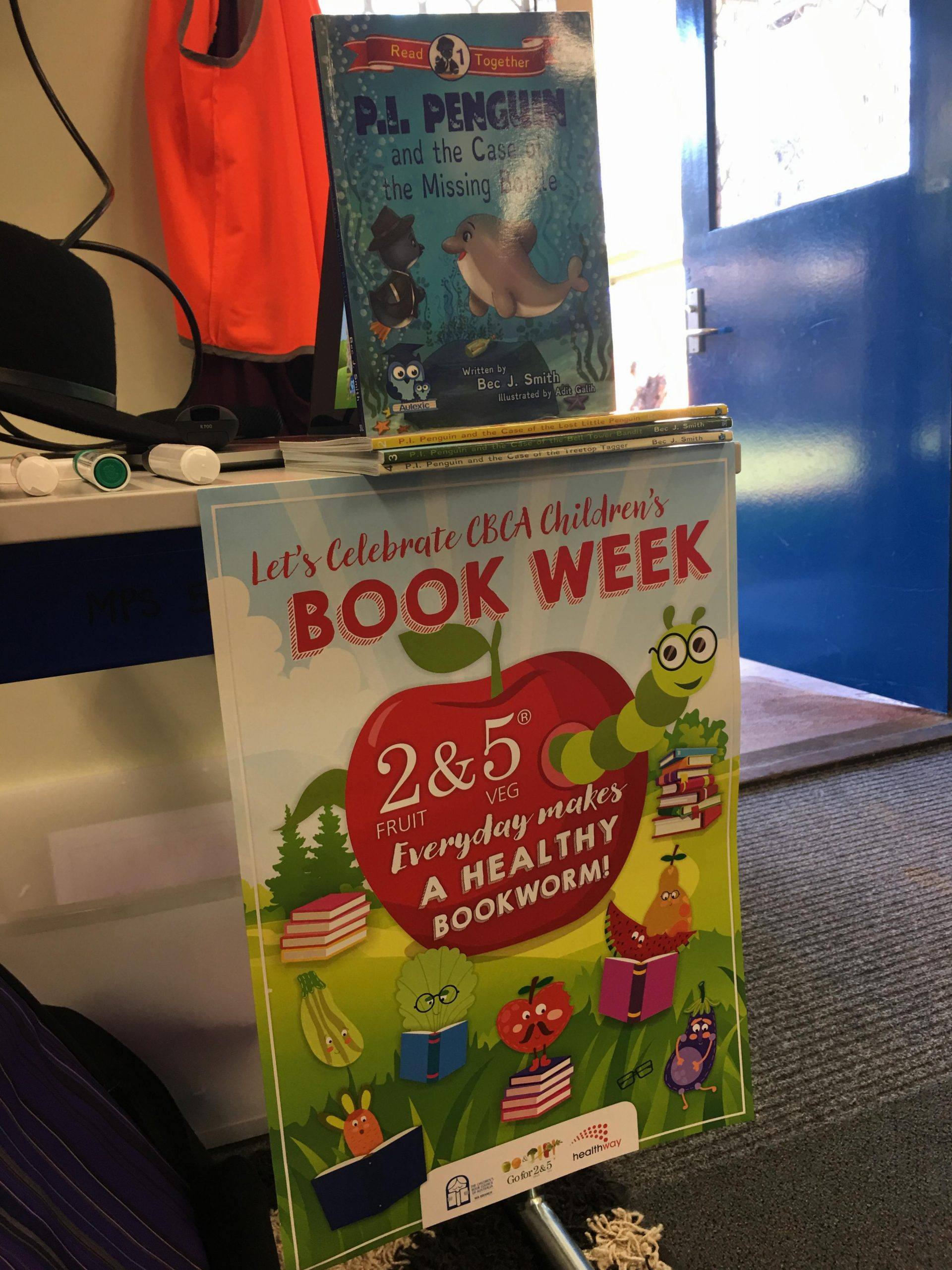 P.I. Penguin books above a Children's Book Week 2017 poster.